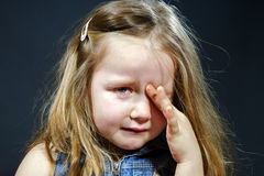 Skriande blond liten flicka med fokusen på henne revor Arkivbild