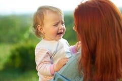 Skriande dottersammanträde på händer för moder` s under solig dag i fältet fotografering för bildbyråer