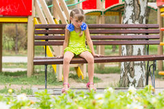Skriande flickasammanträde på bänken på bakgrund av lekplatsen Royaltyfria Bilder