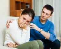 Skriande kvinna, man som tröstar henne Fotografering för Bildbyråer