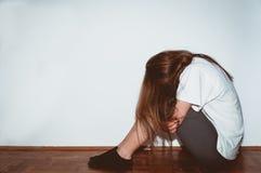 Skriande kvinna som missbrukas som ung känsligt deprimerat och bedrövligt medan henne som bara sitter i hennes rum arkivfoton