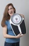 Skriande kvinnlig tonåring som rymmer en viktskala Royaltyfria Foton