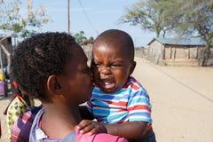 Skriande namibian barn med modern Arkivfoto