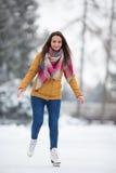 Skridskoåkning för ung kvinna utomhus på ett damm arkivbilder