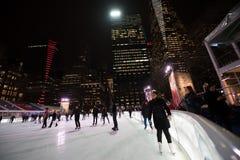 Skridskoåkningisbana och skateboradåkare på Bryant Park i New York Arkivfoto
