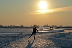 Skridskoåkning Nederländerna på solnedgången Royaltyfri Bild
