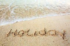 Skriftlig ferie i sand på stranden Fotografering för Bildbyråer