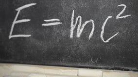 Skriftlig krita för Einsteins formel på en kritisera stock video