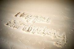 Skriftlig lycklig födelsedag i sand Arkivfoto