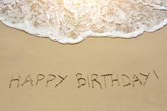 Skriftlig lycklig födelsedag på sandstranden Royaltyfria Foton