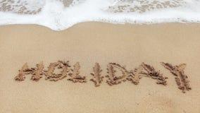 Skriftlig ordFERIE på våt sand av stranden, liten fläck av vatten för vitt hav i bästa del royaltyfri foto