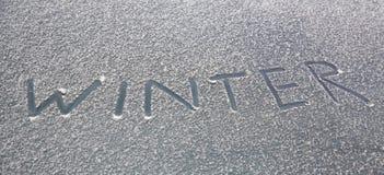 Skriftlig ordvinter på den snöig vindrutan arkivbilder