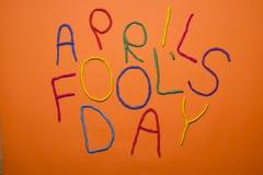Skriftlig rolig dag för stilsortsförsta april dumbommar i plastecine av olika färger Arkivbilder