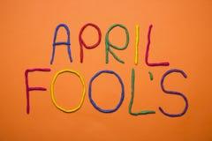 Skriftlig rolig dag för stilsortsförsta april dumbommar i plastecine av olika färger Royaltyfri Fotografi