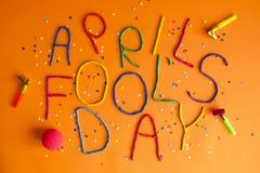 Skriftlig rolig dag för stilsortsförsta april dumbommar i plastecine av olika färger Fotografering för Bildbyråer