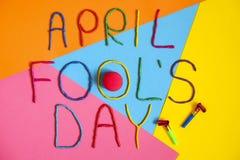 Skriftlig rolig dag för stilsortsförsta april dumbommar i plastecine av olika färger Royaltyfria Bilder