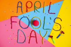Skriftlig rolig dag för stilsortsförsta april dumbommar i plastecine av olika färger Royaltyfria Foton