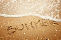 Skriftlig sommar i sanden på stranden Royaltyfria Bilder