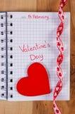 Skriftlig valentindag i anteckningsbok och röd hjärta med bandet, garnering för valentin Arkivfoton