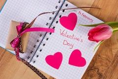 Skriftlig valentindag i anteckningsboken, den nya tulpan, den slågna in gåvan och hjärtor, garnering för valentin Arkivfoto