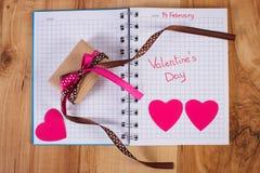 Skriftlig valentindag i anteckningsboken, den slågna in gåvan och hjärtor, garnering för valentin Arkivfoto
