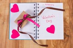 Skriftlig valentindag i anteckningsboken, den slågna in gåvan och hjärtor, garnering för valentin Royaltyfria Bilder