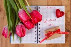 Skriftlig valentindag i anteckningsboken, nya tulpan, den slågna in gåvan och hjärta, garnering för valentin Arkivfoto