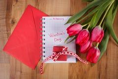 Skriftlig valentindag i anteckningsboken, nya tulpan, förälskelsebokstaven och gåvan, garnering för valentin Arkivfoto