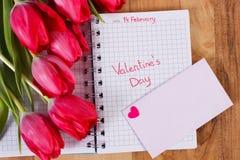 Skriftlig valentindag i anteckningsboken, nya tulpan, förälskelsebokstaven och hjärta, garnering för valentin Arkivbild