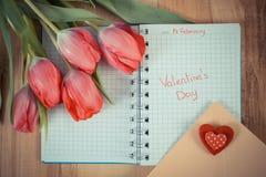 Skriftlig valentindag i anteckningsboken, nya tulpan, förälskelsebokstaven och hjärta, garnering för valentin Arkivfoto