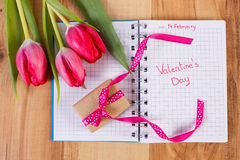 Skriftlig valentindag i anteckningsboken, nya tulpan och den slågna in gåvan, garnering för valentin Royaltyfri Foto