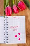 Skriftlig valentindag i anteckningsboken, nya tulpan och hjärtor, garnering för valentin Arkivfoton