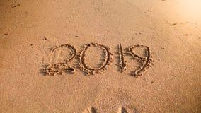 2019 skriftliga nya år på våt sand på havstranden Begrepp av vinterferier, jul och turism arkivfoton