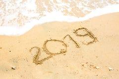 Skriftligt år 2019 på sandstranden med havsvågvatten Royaltyfri Fotografi