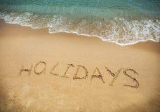 Skriftligt i sand på stranden Den lyckliga mannen tycker om på ferier på havet Royaltyfri Bild