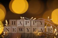 Skriftligt lyckligt nytt år på träkvarteret med ljus och bokehbaksida Arkivbild