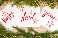 Skriftligt lyckligt nytt år på vita ark Royaltyfri Fotografi