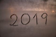Skriftligt numret av det nya året 2019 på ett fönster med en skumsprej arkivfoto