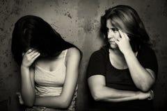 Skrik för tonårs- flicka bredvid hennes ilskna och bekymrade moder Royaltyfri Foto