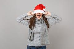 Skrika den unga jultomtenflickan i den gråa tröjahalsduken som täcker ögon med julhatten som in isoleras på grå väggbakgrund fotografering för bildbyråer