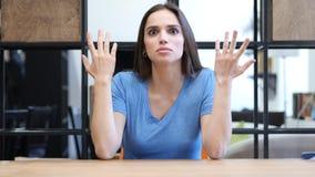 Skrika ilsken ung kvinna som argumenterar in mot kamera, inomhus Royaltyfria Bilder