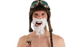 Skrikig man med begränsade ögon med att raka skum på hans hjälm för framsida i flykten och flygskyddsglasögon med rakkniven Royaltyfri Fotografi