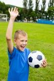 Skrikig pojke som spelar fotboll. Arkivbilder