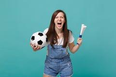 Skrikigt löst kvinnafotbollsfanjubel stöttar upp det favorit- laget med fotbollbollen, röret som isoleras på den blåa turkosvägge royaltyfri foto