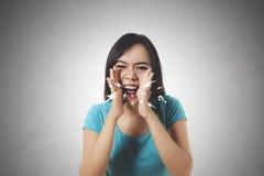 Skrin för ung kvinna genom att använda henne händer Royaltyfri Fotografi