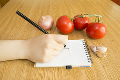 Skriv i anteckningsbok och nya grönsaker royaltyfria bilder