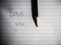 Skriv orden som är förälskade med en blyertspenna arkivbilder