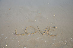 Skriv ordförälskelse på stranden Arkivfoton