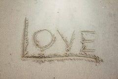 Skriv ordförälskelsen på sanden royaltyfri fotografi
