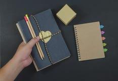 Skriv pappers- anteckningsbokblyertspennor på svart bakgrund Royaltyfri Fotografi